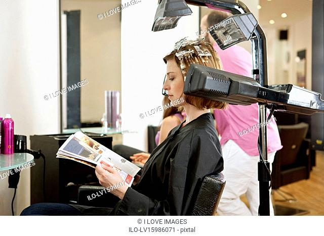 A female client reading a magazine whilst she has her hair coloured in a hairdressing salon