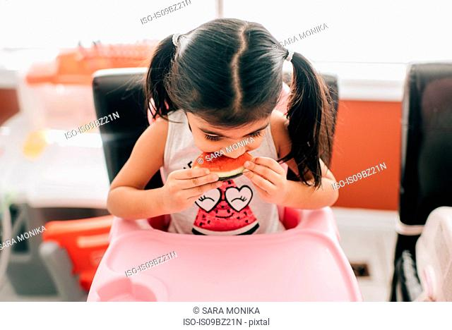Girl in high chair eating water melon