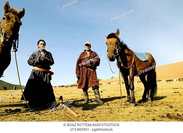 Mongolian nomads enjoy a cigarette break in the vast Mongolian grasslands