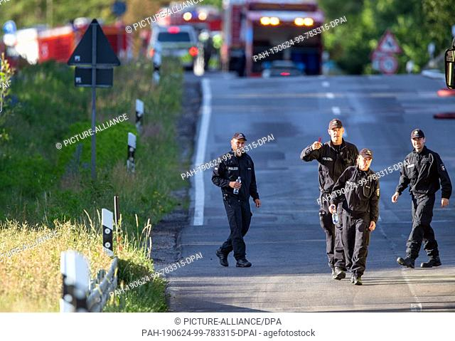 24 June 2019, Mecklenburg-Western Pomerania, Jabel: Policemen walk across a cordoned off road near the crash sites of a Eurofighter near Jabel