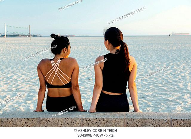 Friends talking on beach, Long Beach, California, US