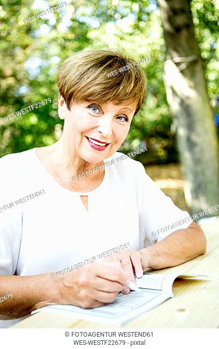 Portrait of smiling senior woman doing a crossword puzzle outdoors