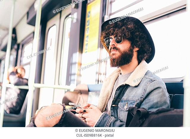 Young man sitting on subway train, using smartphone