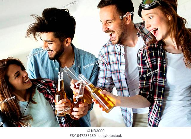 Group of happy young friends having fun and drinking beer at home