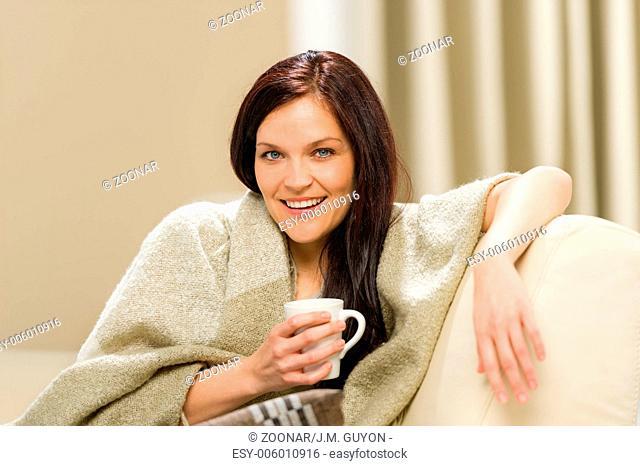 Joyful cozy woman drinking hot drink