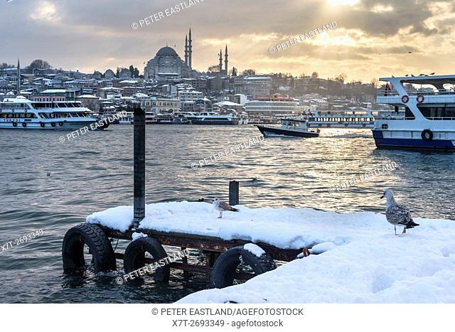Snow covered Karakoy waterfront, looking across the Golden Horn toward the sulimaniye mosque and the Istanbul skyline. Istanbul, Turkey