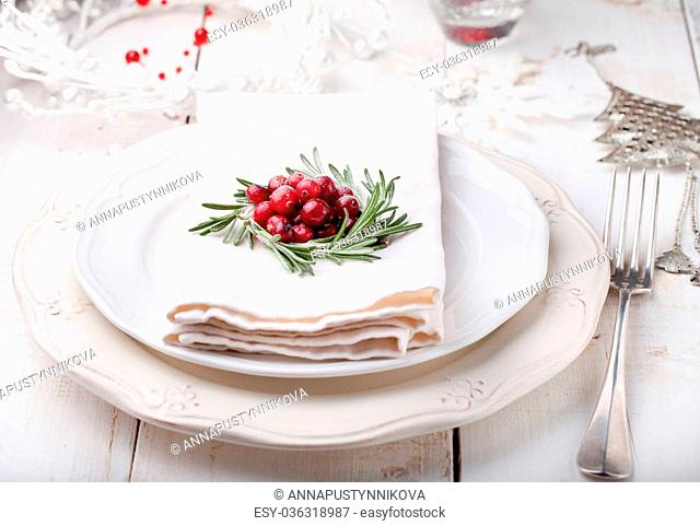 Christmas And New Year Holiday Table Setting with cranberry and rosemary decoration. Holiday decoration