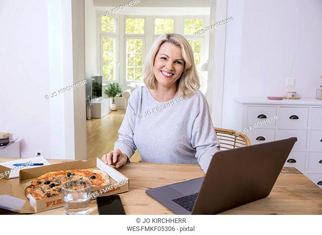 Portrait of smiling blond mature woman at home office having pizza