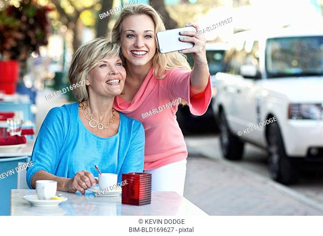 Caucasian mother and daughter taking selfie at sidewalk cafe