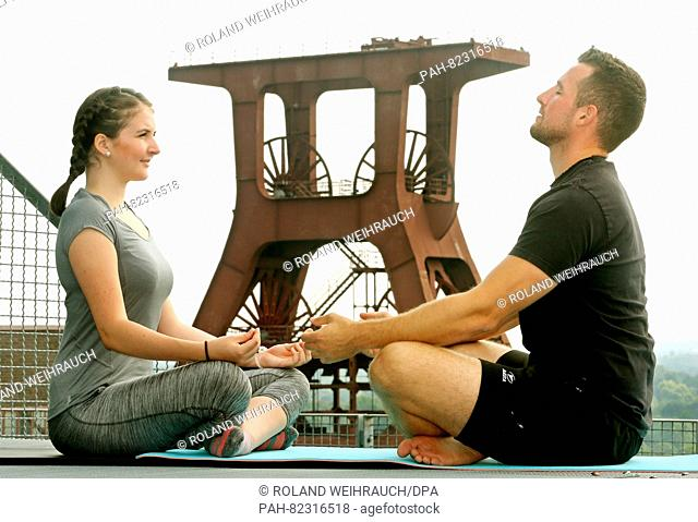 Siblings Madita and Frederik Reimann meditate on the roof of the Zollverein Coal Mine Industrial Complex in Essen, Germany, 27 July 2016