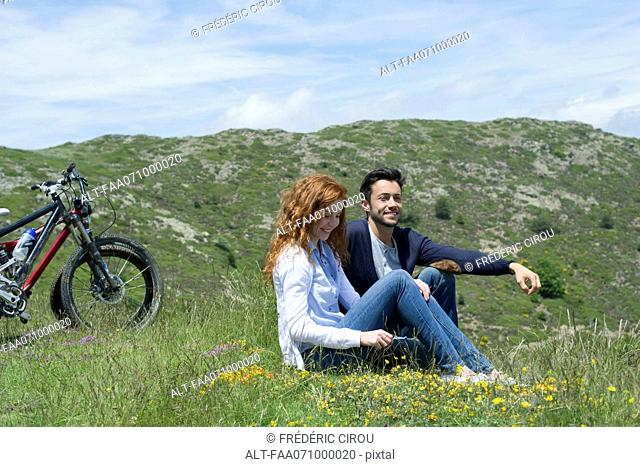 Couple sitting on meadow by mountain bikes