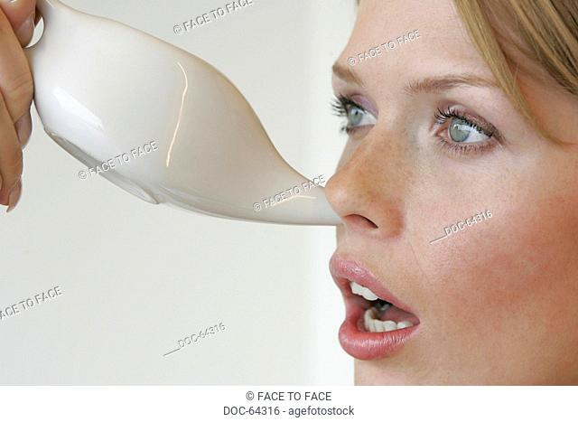 young adult woman makes nasal douche