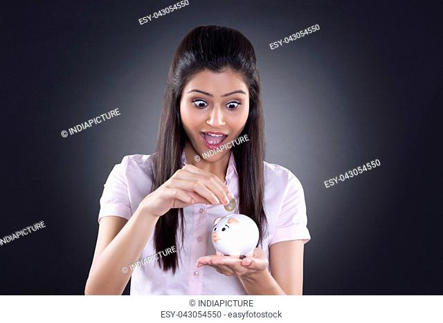 Businesswoman putting coin in piggy bank