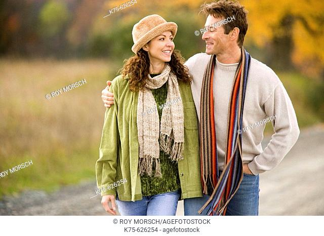 Caucasian couple, age 30's to 40's, country road, autumn, hugging