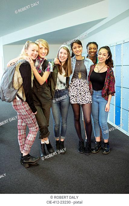 Group portrait of cheerful female students standing in locker room