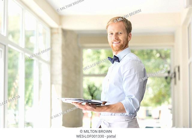 Smiling waiter in restaurant holding tray