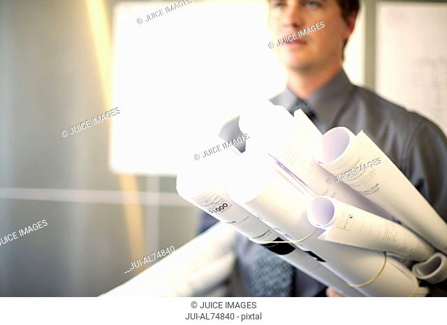 View of a young businessman carrying lots of blueprints under his arms