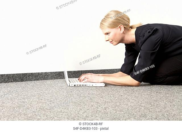 Woman using laptop on floor, Munich, Bavaria, Germany