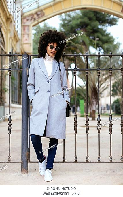 Spain, Barcelona, woman wearing sunglasses standing at a gate