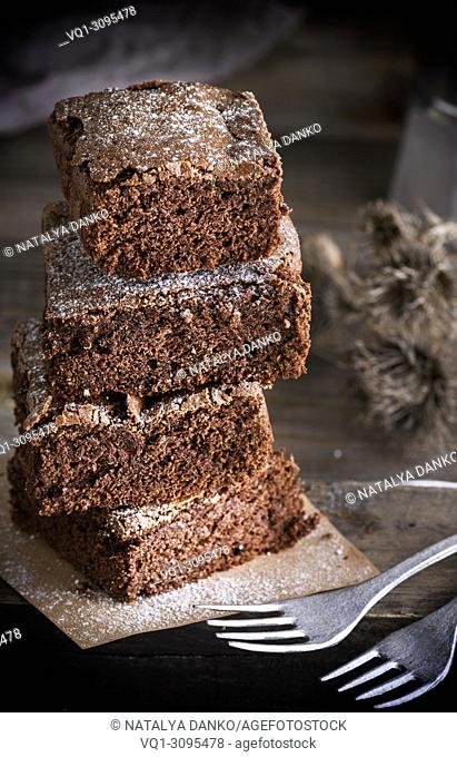 stack of square pieces of chocolate cake baked brownies and two iron forks, close up