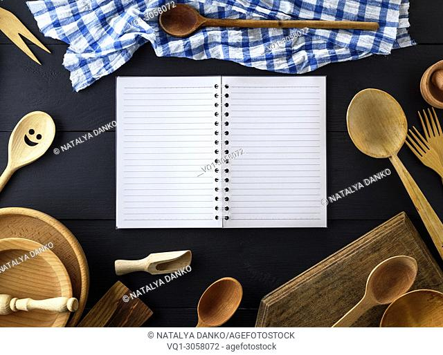 open empty paper notebook with white sheets in a line on a spring in the middle of wooden kitchen items on a black wooden table, top view