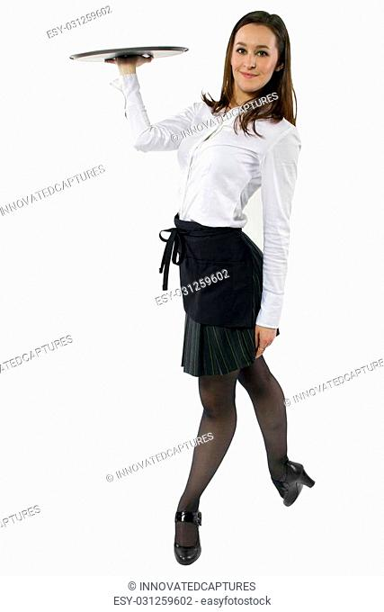 young female waitress dancing and carrying an empty tray