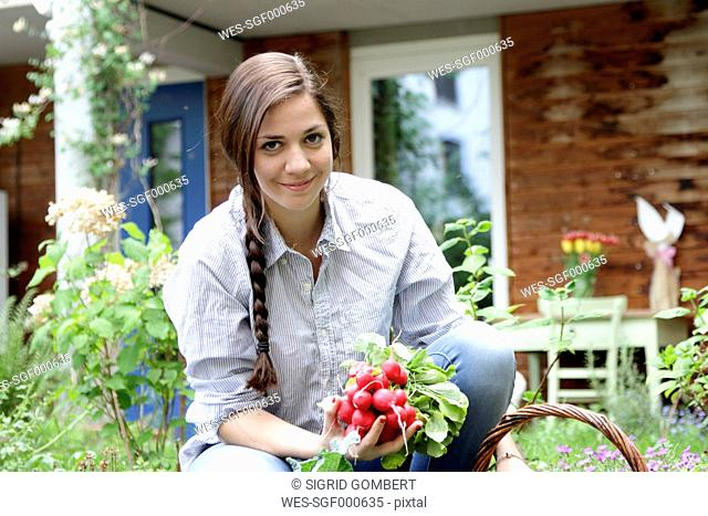 Young woman with red radishes in vegetable garden