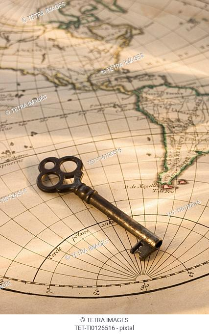Old fashioned key on globe map