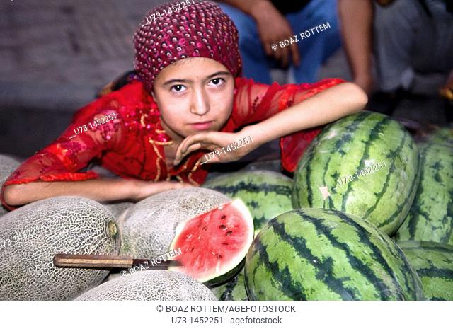 An Uighur girl sitting by tasty melons and watermelons sold on the streets of Kashgar