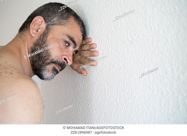 Depressed middle eatsern man leaning against the wall