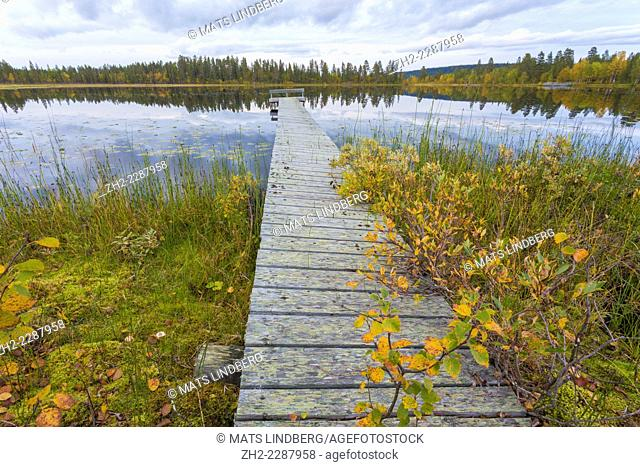 Lake with landing stage in autumn landscape in Gällivare, Sweden