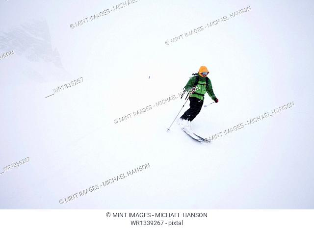 A skier in powder snow in mist and cloud conditions on the Wapta Traverse, a mountain hut to hut ski tour in Alberta, Canada
