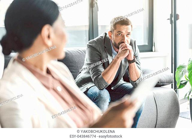 Sad thoughtful male patient sitting on couch and looking up with bewilderment. Psychologist locating afore him. Portrait. Copy space on left side