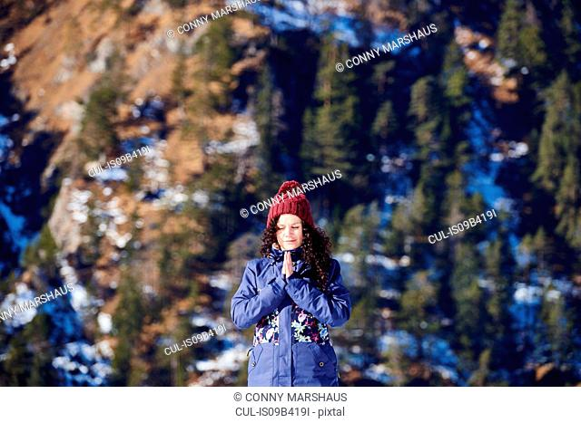 Woman in knit hat practicing yoga, meditating in front of snowy mountain