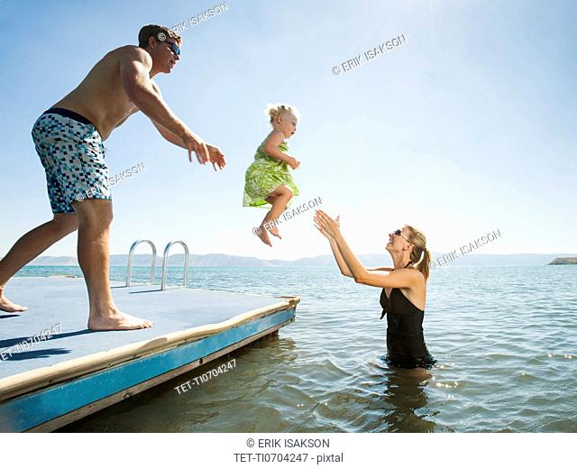Parents playing with their daughter 2-3 in lake