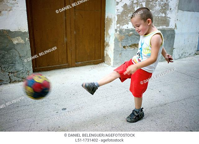 boy playing football on a village, Ludiente, Castellón, Spain