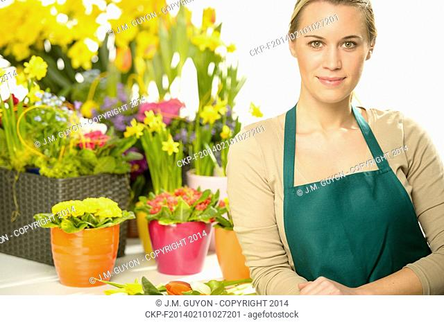 Florist with spring potted flowers colorful looking at camera