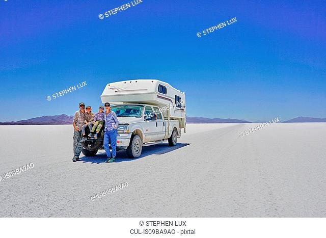 Portrait of family, standing in front of parked recreational vehicle, Salar de Uyuni, Uyuni, Oruro, Bolivia, South America