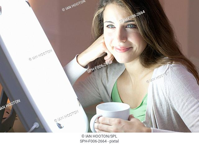 MODEL RELEASED. Light therapy. Woman sitting in front of a light box to treat seasonal affective disorder (SAD)