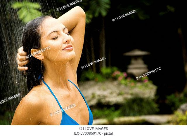 Beauty portrait of a woman in a tropical shower setting