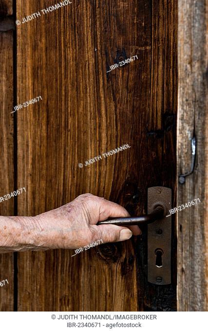 Hand of an elderly woman pushing a doorknob