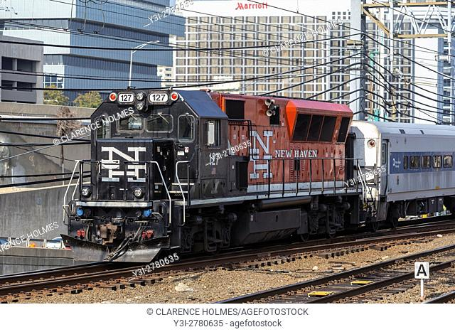 An Metro-North BL20GH diesel locomotive in New Haven livery pulls a short train into Stamford Station in Stamford, Connecticut