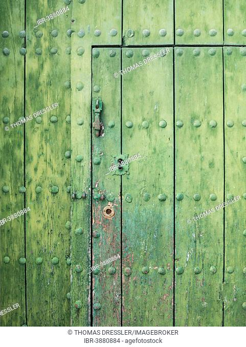Detail of a wooden door with iron spikes, Málaga province, Andalusia, Spain