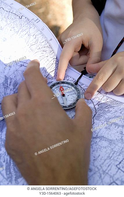 Adult and Child hands reading a compass on a map