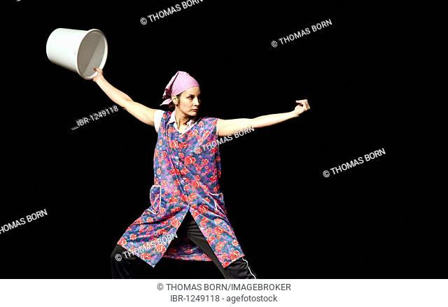 Kung Fu fighter dressed as a cleaning lady with a bucket as a weapon in her hand performing on stage, Chinese New Year festival of the Kung Fu Academy in the...