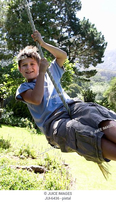 Boy 8-10 swinging on garden rope swing, smiling, portrait