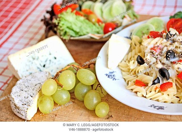 Fusilli with white mushroom sauce  White mushroom sauce with fresh basil and thyme, tomato, black olives and leeks  Shrimp edges the plate  Red and green grapes...