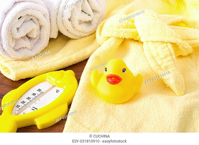thermometer, rubber ducky and a children's bathrobe on the table