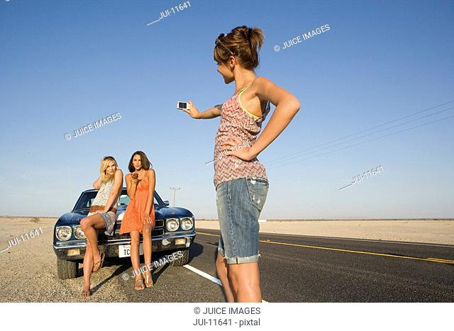 Young woman taking photograph of friends by car on desert road, low angle view