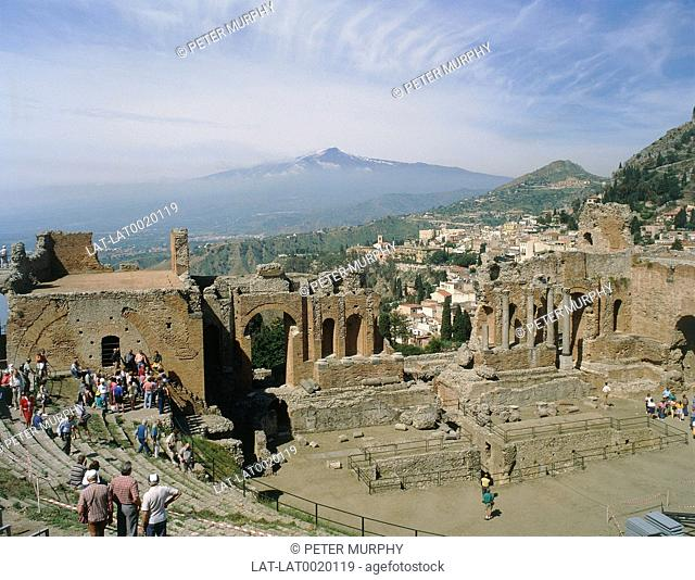 Roman amphitheatre. Brick and stone ruins. Snow capped mountain in distance. Crowd of people